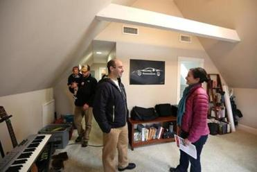 Josh Ziperstein spoke with his wife, Jessica Zeidman, as Kevin Neary carried one of his twins into the room. All were at an open house for 10 Lee St., Unit 2.